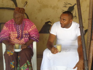 Ezeozo supported by his father sipping the omumu drink