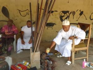 Diopka praying with Omumu while Ezeozo looks on